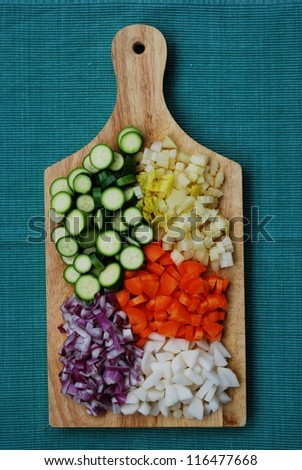 Colorful vegetables palette on wooden trencher on green background
