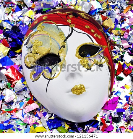 colorful venetian mask on a pile of metallic confetti of different colors