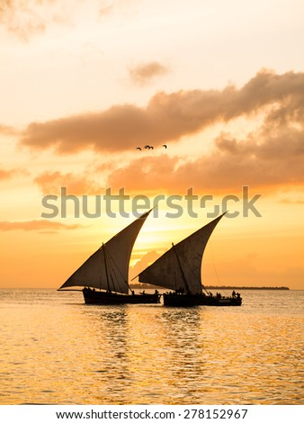 Colorful vertical photo of two traditional Tanzanian dhow boats on open sea on Indian Ocean close to Stone Town on Zanzibar island, Tanzania in East Africa, at orange sunset.