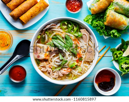colorful vietnamese pho bo with beef and spring rolls
