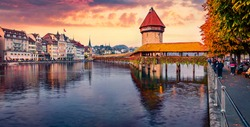 Colorful view of famous old wooden Chapel Bridge (Kapellbrucke), landmark 1300s wooden bridge with grand stone water tower decorated with 17th-century art. Lucerne cityscape, Switzerland.