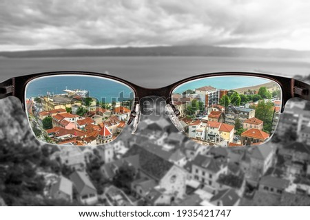 Colorful view of red roofs and blue sea in Croatian city focused in women's glasses and monochrome background. View through eyeglasses. Better vision concept. Different world perception. Stock fotó ©
