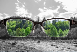 Colorful view of river and forest focused in women's glasses and monochrome background. View through eyeglasses. Better vision concept. Different world perception.