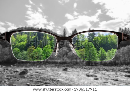 Colorful view of river and forest focused in women's glasses and monochrome background. View through eyeglasses. Better vision concept. Different world perception. Stock fotó ©