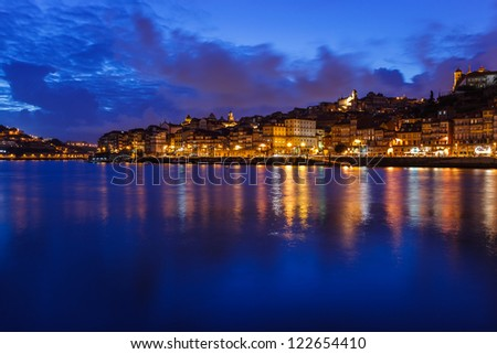 Colorful view of sunset along the riverfront with lights reflecting in the Douro River in Porto, Portugal
