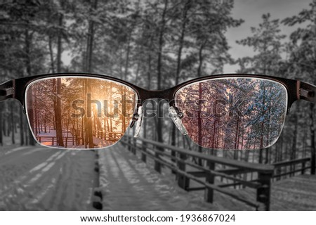 Colorful view of sunset in winter forest focused in women's glasses and monochrome background. View through eyeglasses. Better vision concept. Different world perception. Stock fotó ©