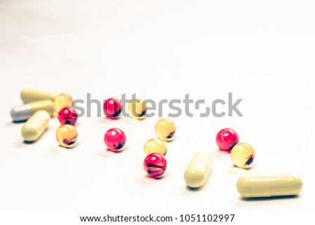 Colorful vitamin pills, medicine tablets and capsules on an abstract white background. Healthcare, medical and pharmaceutical concept. Detailed closeup studio shot with soft selective focus. Toned #1051102997