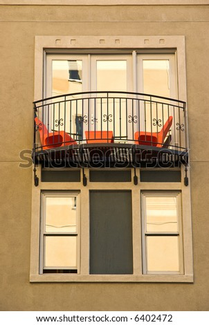 Colorful wall of modern building with window and balcony with furniture