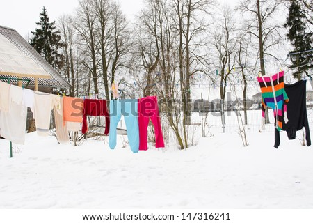 colorful washed wet clothes loundry dry hang on rope in house yard in winter.