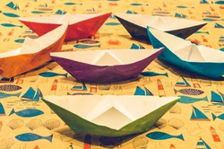 Colorful water color painted paper boats on cartoon background symmetrically arranged
