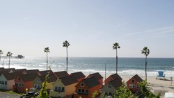 Colorful waterfront cottages, Oceanside California USA. Multicolor bungalow huts, summer sea, beachfront lodging. Many vacation houses on beach, ocean waves and palm trees. Lifeguard tower, watchtower