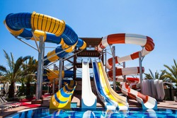 Colorful waterpark tubes and pool in tropical aquapark