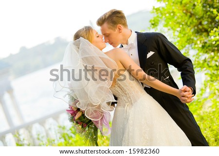 Colorful wedding shot of bride and groom dancing - stock photo