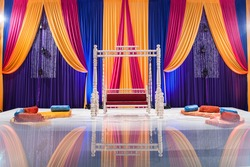 Colorful wedding stage with elegant curtain drawings, seating, and pillows