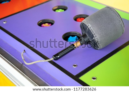 Colorful Whack a Mole game at a carnival and arcade, with padded mallet and space for text on the left Stockfoto ©