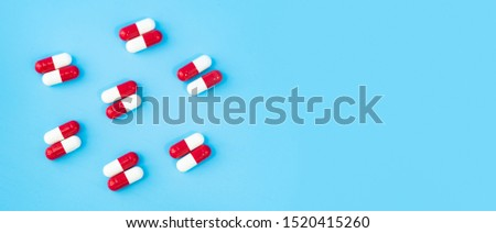 Colorful white and red assorted pharmaceutical medicine pills.capsules on blue background.Capsules Vitamin And Dietary Supplements.