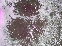 Colorful white bath foam with bubbles on the ground. Effect of space and galaxy. Abstract art. Beautiful pink soap background with waves and foam. Washing suds texture on the dark surface