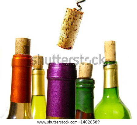 Colorful wine bottles and corks closeup on white