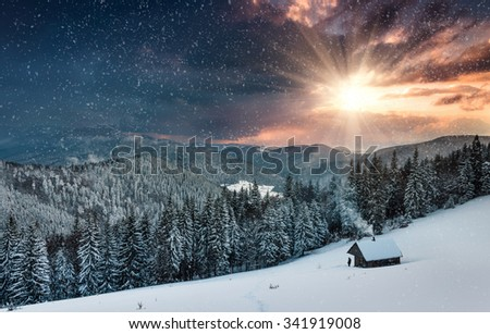 Colorful winter evening in the mountains at sunset. Dramatic overcast sky and snowing. View of the old farm and tourist near. #341919008