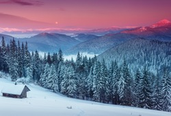 Colorful winter morning in the mountains. View of the moon and the snow-capped peaks.