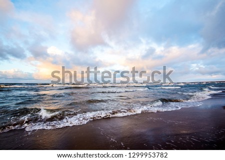 Colorful winter sunset. Cold stormy waves and clouds over the Baltic sea, Latvia