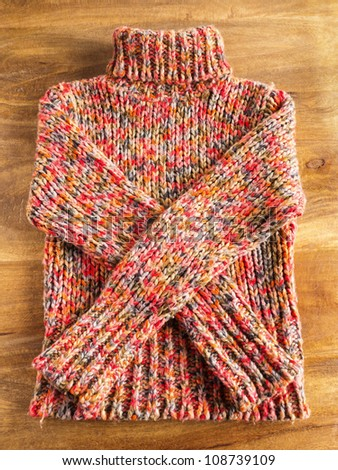 Colorful winter sweater on wooden table
