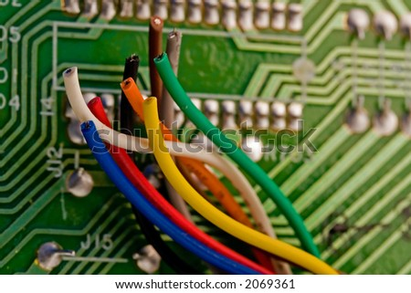 Colorful wires in front of a computer circuit-board