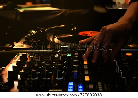 Colorful with hand adjust mixer drop beat by turntable DJ party at nightclub with lowkey and soft focus