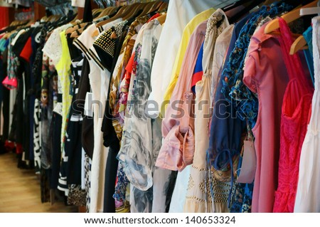 Colorful women's dresses on hangers in a retail shop
