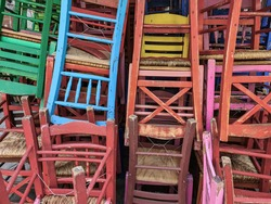 Colorful wooden chairs stacked outside. Day sunny view of tavern style chairs in random disarray and bright colours in Greece.