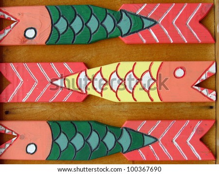 Colorful wooden fence detail, fish shape ornament. Taken in Karelia, Russia.