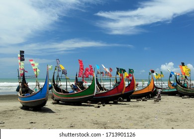 Stock Photo - Colorful Wooden Fishing Boat On a Cox's Bazar Sea Beach With Blue Sky Background in Bangladesh.