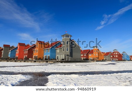 Colorful wooden houses at the frozen and snow covered water in Holland.