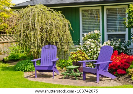Colorful wooden lawn chairs at the front ( back ) yard.