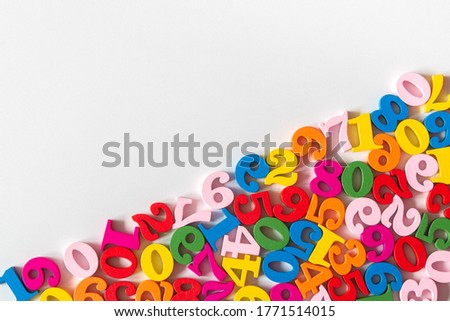 Photo of  Colorful wooden numbers on part of background with copy space. Numbers texture abstraction on part of board. Top view of multicolor numbers from zero to nine. Mathematic topic. Back to school concept