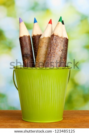 Colorful wooden pencils in pail on wooden table on bright background - Shutterstock ID 123485125