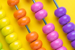 Colorful wooden pink and orange abacus beads on yellow background, business financial or accounting profit and loss concept, or use in education school arithmetic symbol.