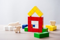 colorful wooden puzzle blocks toy and wooden animals, wooden construction blocks with geometric shapes.