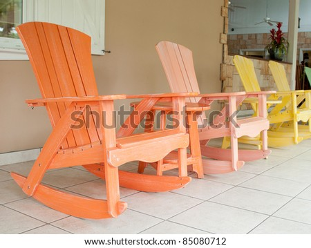 colorful wooden rocking chairs on a porch (usual setting on a tropical ...
