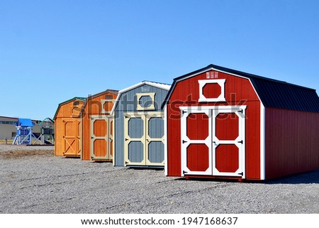 Colorful wooden sheds in row on display. American shed is typically a simple, single-story roofed structure in a back garden or on an allotment that is used for storage, hobbies, or as a workshop.  Foto stock ©