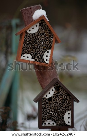 Colorful wooden snow covered house for insects in the wintry garden. #1024262407
