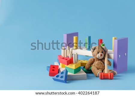 Colorful wooden toy building blocks with toys on blue