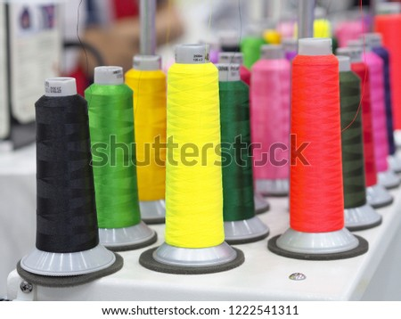 Colorful wool and bobbins with colored thread  spools on desk used in textile industry for industrial textile machines.   #1222541311