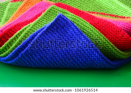 Colorful wool cloth on a green background. Textile pattern, wool cloth.  #1061926514