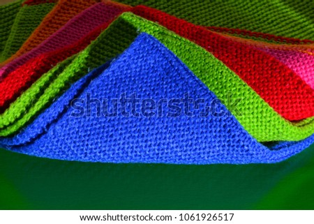 Colorful wool cloth on a green background. Textile pattern, wool cloth.  #1061926517