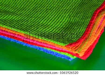 Colorful wool cloth on a green background. Textile pattern, wool cloth.  #1061926520