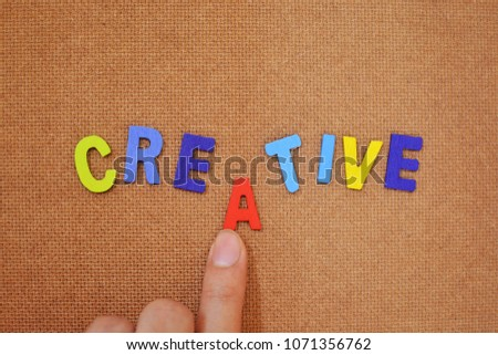 """Colorful words concept. The word """"creative"""" on brown plywood background. A finger pushing an alphabet to complete the word. #1071356762"""