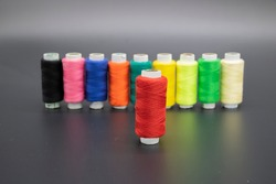 Colorful yarn on spool, yarn on tube, cotton, wool, linen thread, polyester selective focus on red spool