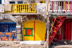 Colorful yellow and blue garage doors in Greek Klima fishermen village - the most colorful village in Greece, with colorful balconies, stairs and traditional whitewashed house walls.
