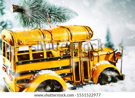 Colorful yellow bus carrying a Christmas tree on the roof to decorate for the festive holiday season driving through a winter snowstorm with copy space for a seasonal greeting